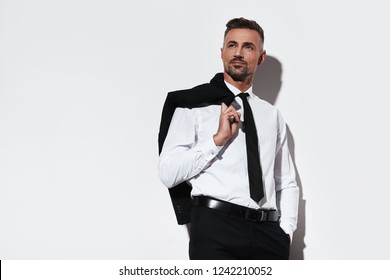 Looking in future. Handsome young man in full suit keeping hand in pocket and looking away with smile while standing against white background