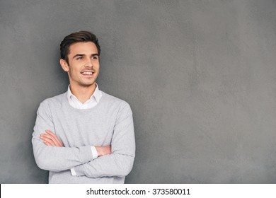 Looking in future with smile. Confident young man keeping arms crossed and looking away with smile while standing against grey background