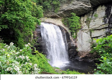 Looking Glass Falls in the Pisgah National Forest, North Carolina, cascades among lush greenery.
