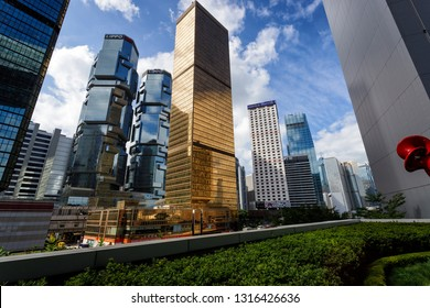 Looking up a the golden skyscraper tower of Bank Negara Indonesia and LIPPO on Hong Kong Island with Merrill Lynch headquarters HQ in the background.