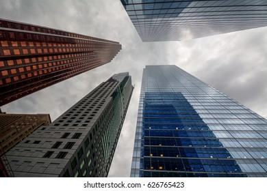 Looking up at grey clouds from the ground in a city with tall buildings
