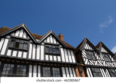 Looking up from the ground to the apex and facade of a typical Tudor style property in England with the familiar black and white frontage. Copy space provided above on a clear blue sky.