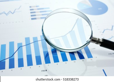 Looking at growth chart with magnifying glass. Graphs, charts and magnifying glass on reflection background.