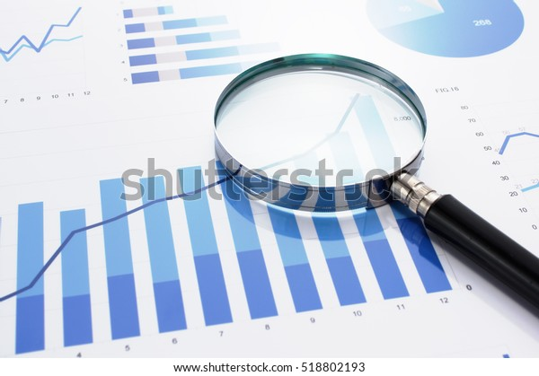Looking at growth chart with magnifying glass. Graphs, charts and magnifying glass.
