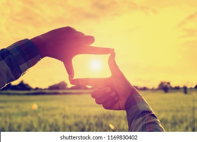 looking hand frame distant view with sunrise over field