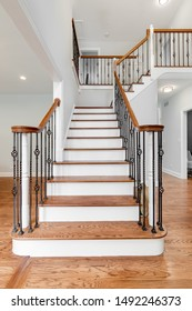 Looking up a household staircase with wrought iron railings, wood banisters, and hardwood floors throughout the house.