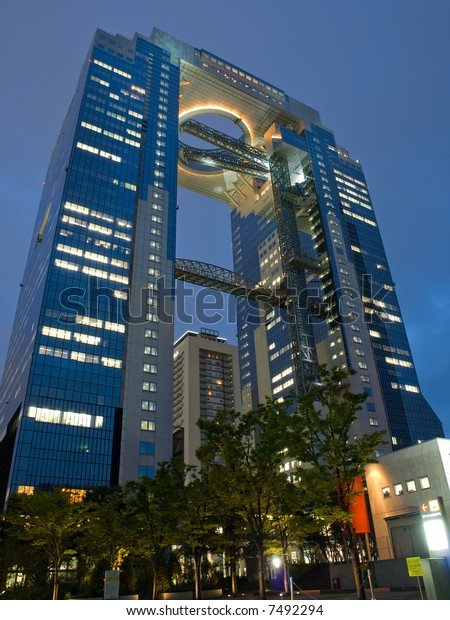 Looking up at the illuminated view of an office high rise building in Umeda Osaka, Japan at dusk