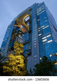 Looking up at the illuminated view of a tall office building in Osaka, Japan at dusk
