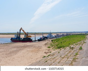 Looking inland towards the town of Wells-next-the-Sea. At low tide in the estuary working boats and small pleasure boats are moored alongside a jetty.