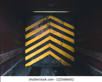looking inside an industrial elevator in a factory, with yellow arrows pointing upwards