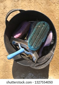 Looking inside a rubber bucket full of horse brushes. Plastic scraper, curry comb, dandy brush, comb and body brush grooming kit for horses and ponies at the stables.