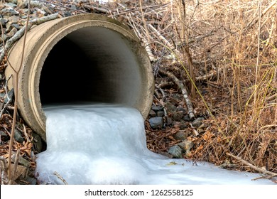 Looking into a frozen culvert. The pipe is about a quarter full of ice which flows out the end.