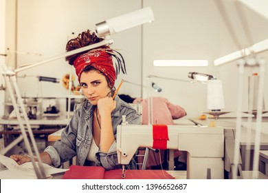 Looking intriguingly. Fashion designer sitting near her sewing machine, with a pencil in one hand and a sheet of paper in the other and frowning at the camera with a tiny sliver of a smile.