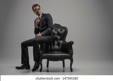 Looking just perfect. Full length of confident young businessmen in sunglasses sitting on the vintage chair while isolated on grey