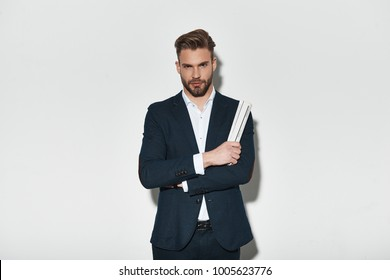 Looking just perfect. Handsome young man in full suit keeping arms crossed and looking at camera while standing against grey background