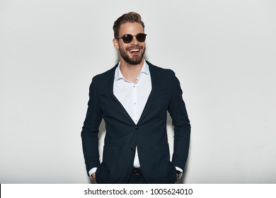 Looking just perfect. Handsome young man in full suit keeping hands in pockets and looking away with smile while standing against grey background