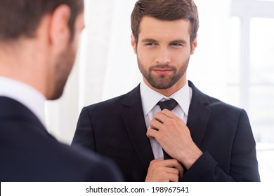 Looking just perfect. Handsome young man in formalwear adjusting his necktie and smiling while standing against mirror