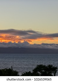 Looking from Lahaina, Maui across the water to glowing sunset clouds behind the island of Lanai in Hawaii.