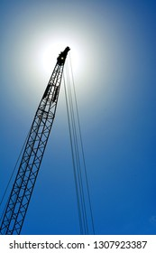 Looking up at a large industrial crane against a clear blue sky with a sun halo and starburst.