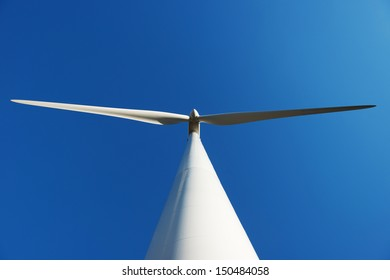 Looking up to a large wind turbine with a clear blue sky in Portugal