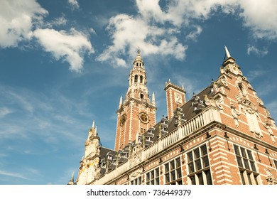 Looking up at the Library at the Catholic University of Leuven (Universiteitsbibliotheek) in Leuven, Belgium with stepped Dutch gables. Blue sky and puffy clouds.
