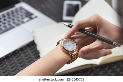 looking at luxury watch on hand check the time writing business information in notepad at workplace.concept for managing time organization working,punctuality,appointment.fashionable wearing stylish