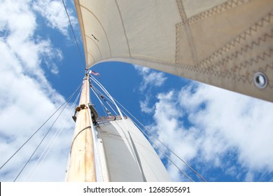 Looking up the mast on a traditional gaff rigged yacht / sailing boat, against a blue sky with little white clouds. It is windy and bright, and the focus is on the flag fluttering at the masthead