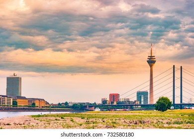 Looking at Media Harbor at Rhine-River in Dusseldorf in Germany. Rhine-Tower and famous buildings in gentle sunset light. Beautiful and colorful cityscape of the german city