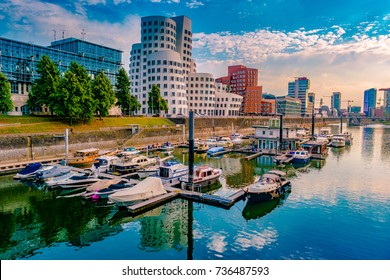 Looking at Media Harbor at Rhine-River in Dusseldorf in Germany. Media Harbor with Rhine-Tower and famous buildings in gentle sunset light with their reflection in the water. Beautiful and colorful