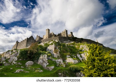 Looking up at medieval castle ruins, perched atop rock outcrop with big blue sky and puffy white clouds - Rock of Cashel, Ireland