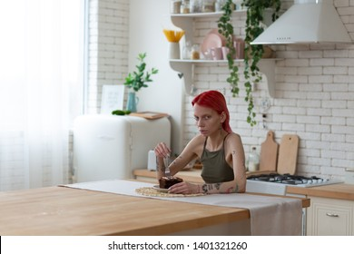 Looking miserable. Red-haired extremely skinny woman looking miserable after suffering from anorexia