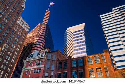 Looking up at a mix of modern and old buildings in Baltimore, Maryland.