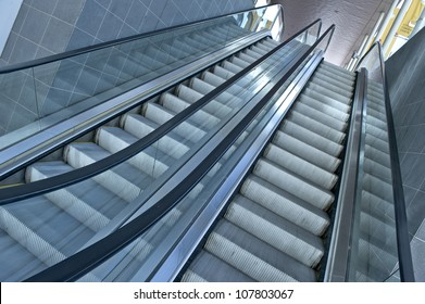 Looking up a modern, metal and glass excalator.