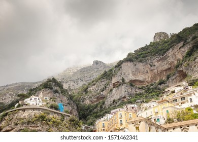 looking up at the mountains with house build into the cliff side in positano in italy