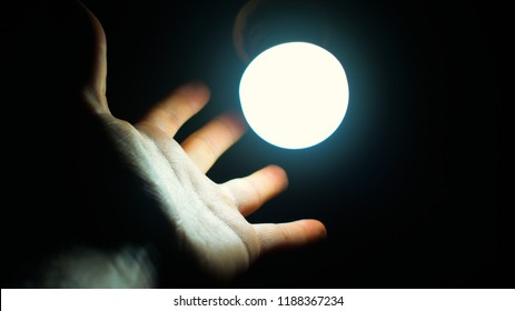 Looking for new ideas. Finding new ideas. Pursuing new ideas. New opportunity. Hand near luminous light bulb on dark background. Conceptual metaphor.