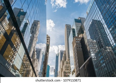 Looking up at New York City skyscapers along 42nd Street on a sunny day.