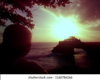 Looking At Ocean Sunset Panorama of Batu Bolong Temple at Tanah Lot, Tabanan, Bali, Indonesia
