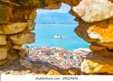 Looking at the old city of Nafplio, Greece through a stone window.
