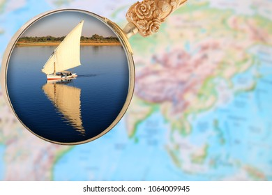 Looking in on a fellucca on the Nile River with a magnifying glass or loop over an atlas in Egypt, Africa