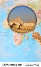 Looking in on the Pyramids of Egypt at Giza through a magnifying glass over an atlas map Africa