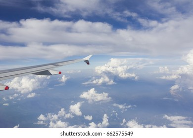 Looking out of aircraft window at wing flying in a bright blue fluffy clouded sky