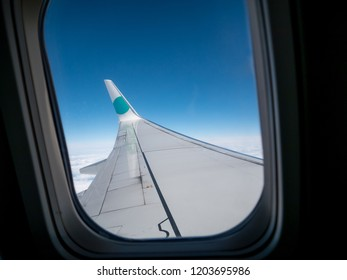 Looking out an airplane window, with blue sky