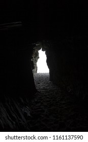 Looking out of a dark cliff cave at the sea