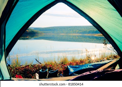 Looking out of open tent door upon calm lake in morning sunshine.