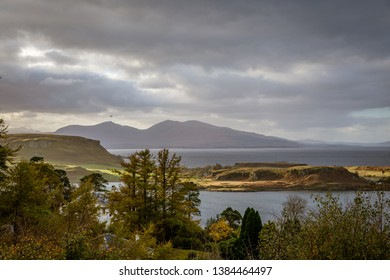 Looking out over the harbor of Oban with dark overcast skies and bright sunlight highlighting some land in Oban, Argyll and Bute, Scotland, United Kingdom