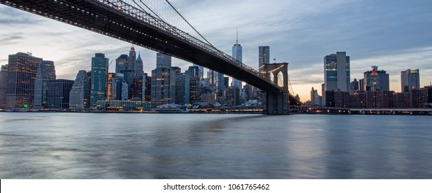 Looking out over New York City's East River just after sunset, the Brooklyn Bridge leads into lower Manhattan.