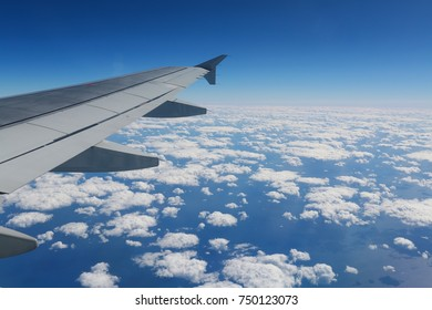 Looking Out Over the Wing of a Commercial Airline Jet to the Atlantic Seaboard under a Blanket of Scattered White Clouds