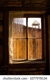 Looking Out a Rustic Wooden Western Window Frame with Tattered Lace Curtains