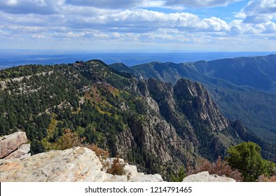 looking out at the sandia peak tramway terminus,  forest,and granite peaks  on a fall day from  sandia peak, new mexico