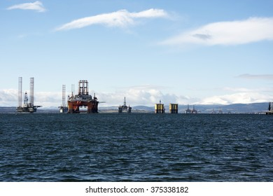 Looking out to sea we see a range of different types of North Sea oil drilling rigs and accommodation rigs,lined up in a row following the deep water channel in the Cromarty Firth, Highlands Scotland.